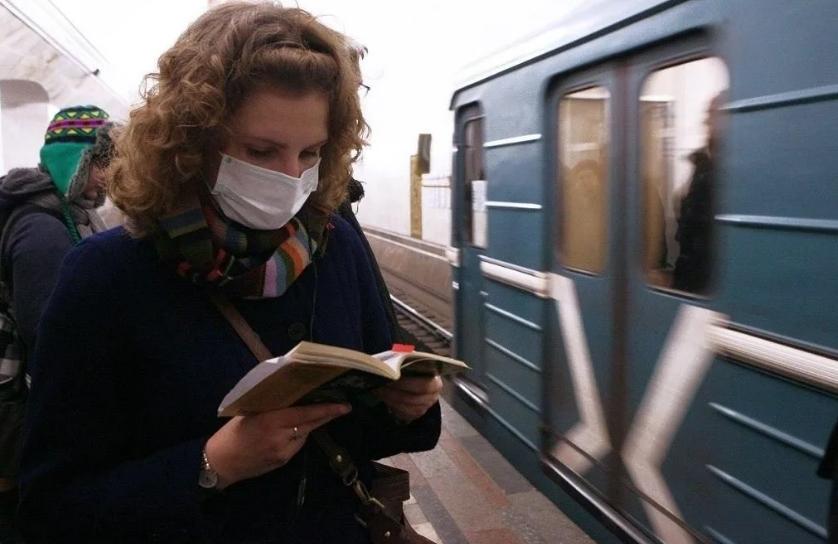 Девушка в маске перед вагоном метро